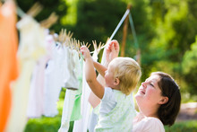 Mother & Child Hanging Clothes...