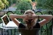 canvas print picture - junge blonde Frau entspannt, Füße hoch, vor Laptop auf Balkon