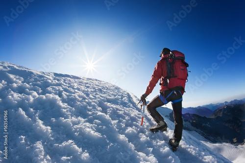 Poster de jardin Alpinisme Mountaineer reaches the top of a high mountain peak.