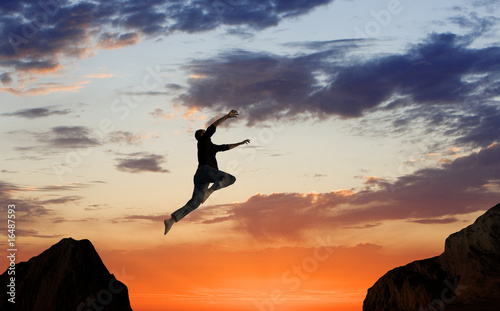 Fotografie, Tablou  Man Leaping Mid-air on Mountainside