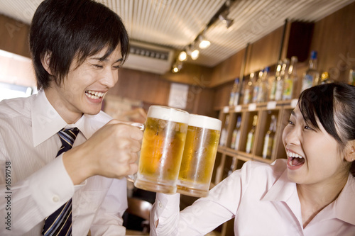 Fotografía  ビールで乾杯するビジネスマンとビジネスレディ