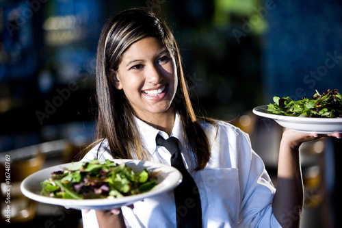 Staande foto Restaurant Hispanic waitress serving two plates of salad in a restaurant