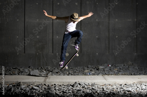 Skateboarder doing an ollie on walking path