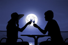 Pair Silhouette Is Held By Goblet With Wine On A Moon Night