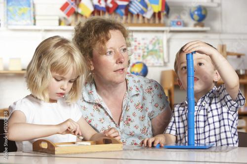 Aluminium Prints Amusement Park Adult Helping Two Young Children at Montessori/Pre-School