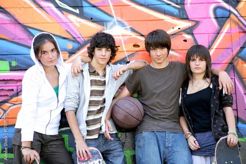 Photo Adolescents devant un mur de graffitis