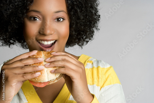 Staande foto Kruidenierswinkel Happy Young Woman Eating Burger