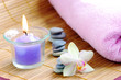 spa concept with candles orchids towels and stones on wet wooden