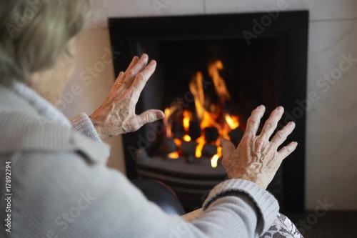 Carta da parati Senior Woman Warming Hands By Fire At Home