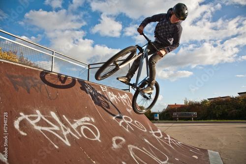 Jugendlicher springt an der Halfpipe mit dem Dirtbike Poster Mural XXL