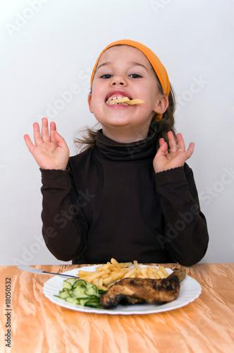 Fényképezés  Kleines Mädchen beim Fastfood essen