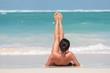 Kobieta leżąca na plaży na plecach z uniesionymi nogami