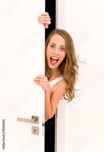 Photo  Young woman peeking through door