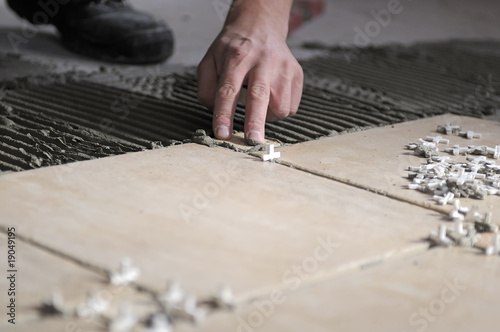 Close Up Of Hand Of Worker Putting Tiles On The Floor Buy This