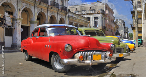 Photo Stands Old cars Havana street with colorful old cars in a raw