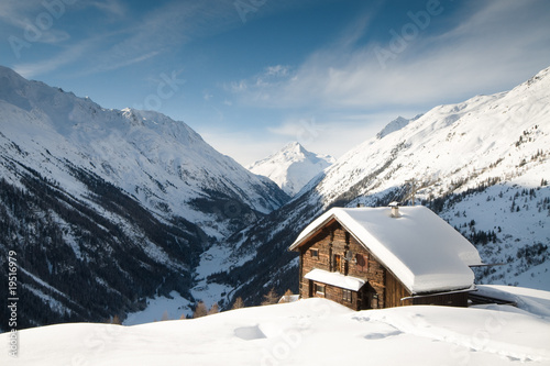 winterscene of alpine valley with snow coverd cabin #19516979