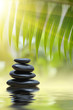 Grean bamboo leaves over zen stones pyramid over water