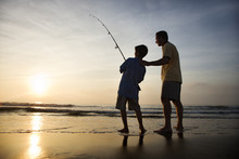 Man And Young Boy Fishing In S...