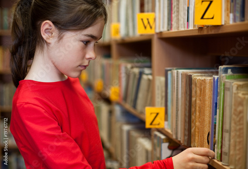 Fotografía  Young girl looking for books in library
