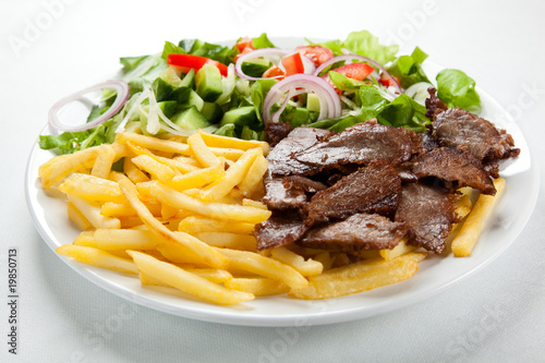 Photo sur Toile Plat cuisine Grilled meat with fried potatoes and vegetables