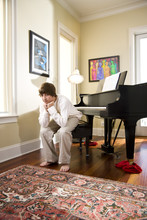 Fourteen Year Old Boy At Home Sitting On Piano Bench