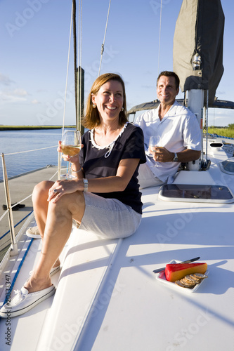 Fotografie, Obraz  Mid-adult couple sitting on deck of boat enjoying drink