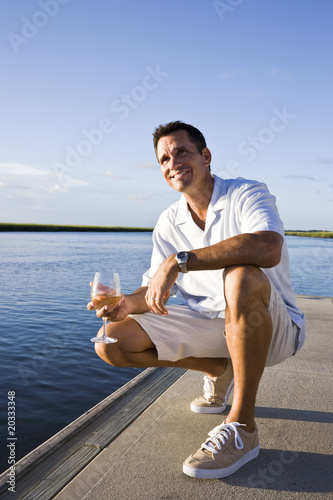 Fotografie, Obraz  Mid-adult man on dock by water enjoying drink on sunny day
