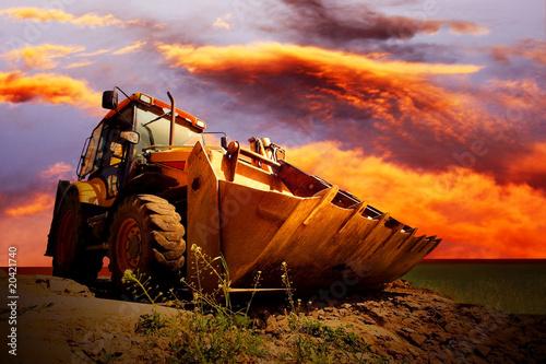 Fényképezés  Yellow tractor on golden surise sky