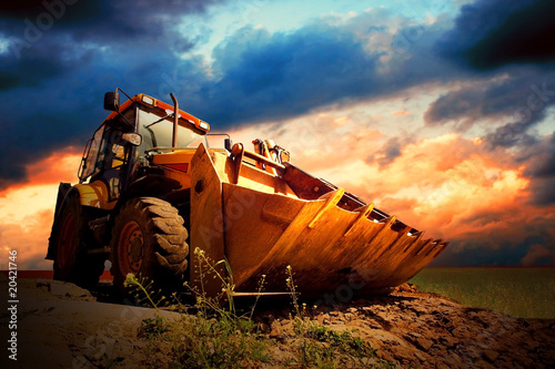 Leinwand Poster  Yellow tractor on golden surise sky