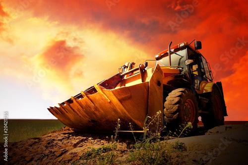 Vászonkép  Yellow tractor on golden surise sky
