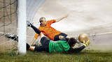 Fototapeta Sport - Shoot of football player and jump of goalkeeper on the field of