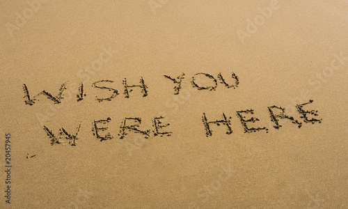 Photo  Wish You Were Here written in sand