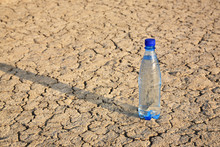 The Bottle  With A Shadow On The Dry Cracked Ground