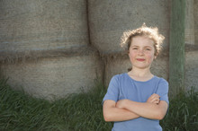 Little Girl Standing In Front Of Bales Of Hay