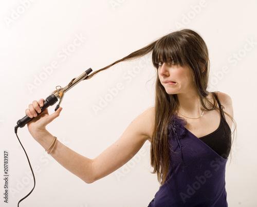 Obraz na plátne jeune femme utilise un fer à friser