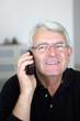 Portrait d'un homme senior souriant avec téléphone portable
