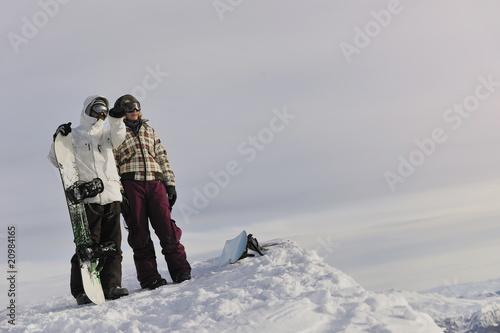 Tuinposter Wintersporten snowboarder's couple on mountain's top