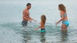 family standing in sea and plaiying with water, join hands