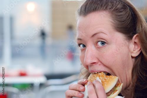 Fotografija  woman is gobbling hamburger down