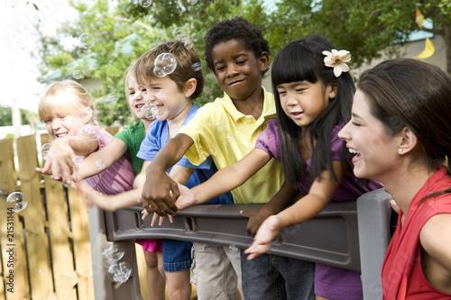 Photo  Preschool children playing on playground with teacher