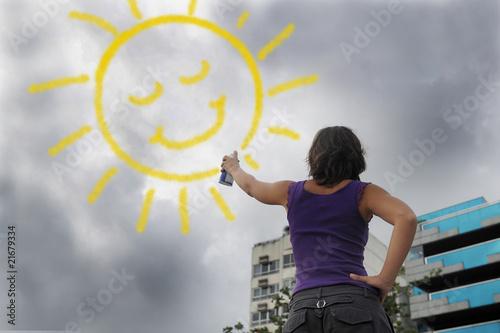 Fotografia  woman painting the sun onto the cloudy sky