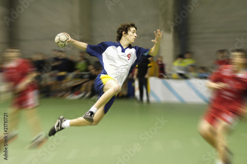 Obraz na plátne young handball player on a match jumping to score a goal