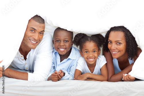 Fotografia  Merry family having fun lying down on bed