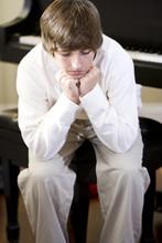 Sad Teenage Boy Sitting With Chin On Hands