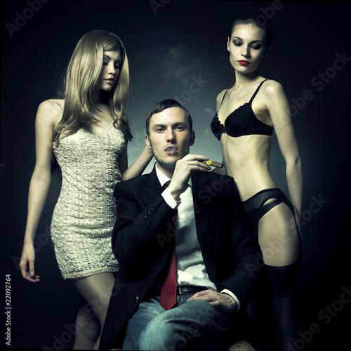 Obraz Przystojny mężczyzna i dwie kobiety - fototapety do salonu
