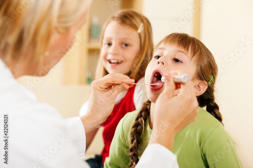 Fotografia  Pediatrician doctor examining throat of girl