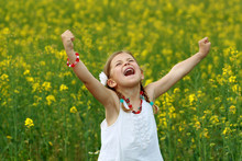 Pretty Young Girl Screaming With Delight In A Rapeseed Field