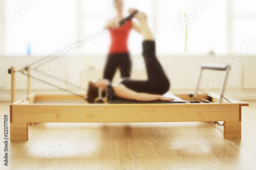 Photo  Plilates reformer in use by two women, soft focus