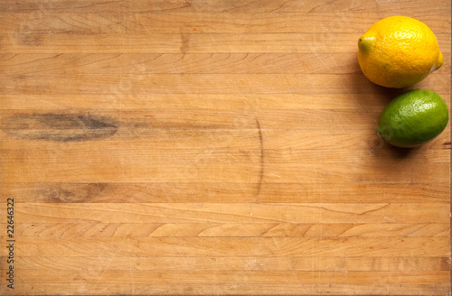 Valokuva  Lemon and lime on a worn butcher block cutting board