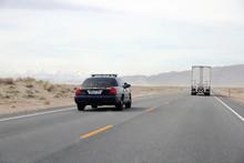 Police Car Patrol On High Way Cross Desert.